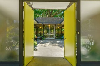 An H-shaped 1960s Eichler home has bright, lime-green double doors that open out onto the signature Eichler features: floor-to-ceiling glass, patios, gardens, concrete slab floors, tongue-and-groove ceilings, and post-and-beam interiors.
