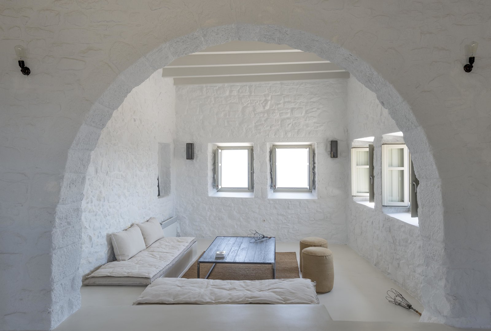 Living Room, Bench, Coffee Tables, Wall Lighting, Concrete Floor, Ottomans, and Rug Floor Resting along the crest of a volcanic crater on the little-known island of Nisyros in the Aegean Sea, Villa Nemésis marries the mystique of ancient Greece with modern design.  Best Photos from Stay at a Greek Island Villa Among the Ruins of a 14th-Century Castle