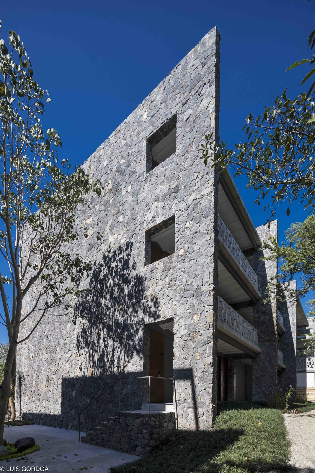 Exterior and Stone Siding Material Located in Jiutepec, Morelos, Mexico, on the site of an old poultry farm, the hotel is composed of five sturdy stone volumes that are separated by well-ventilated, sun-drenched courtyards.   Photo 2 of 12 in A New Hotel in Morelos Combines Local Mexican Elements With Brutalist Architecture