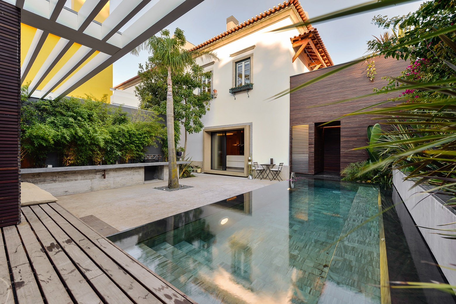 Outdoor, Small, Back Yard, Trees, Decking, Gardens, and Swimming The result is a bright, Portuguese home designed in a clean, formal style, where contemporary interiors exist in harmony with the house's historical shell.  Best Outdoor Gardens Decking Photos from An Architect Renovates His 1920s Home in Portugal, While Preserving the Exterior Shell
