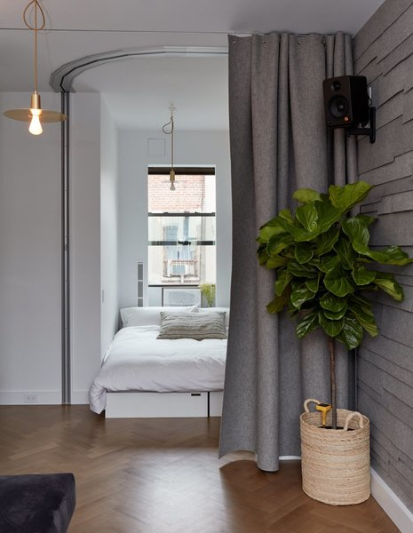 Small space champion Graham Hill's 350-square-foot apartment has an office that flips into a sleeping corner with seating cubes that can be arranged to form a bed and a curved Hufcor accordion door.