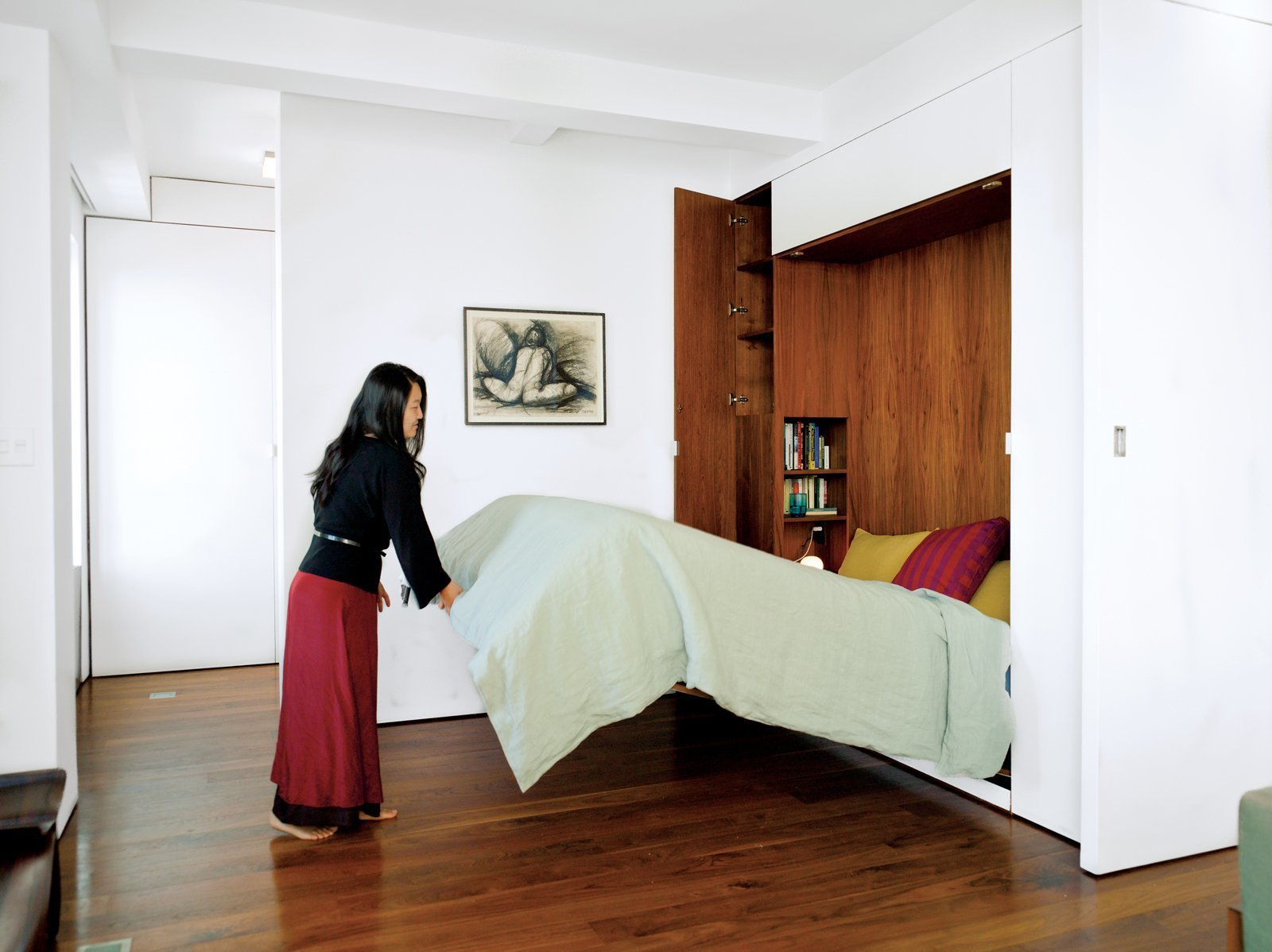 Bedroom, Bed, Shelves, Ceiling Lighting, Storage, and Dark Hardwood Floor An architect couple uses multifunctional furniture and a hydraulic Murphy bed with secret compartments to keep the exterior walls uncluttered and achieve a clean and lean look in their 650-square-foot Chelsea apartment.  Photo 7 of 11 in 11 Hidden Beds in Small Homes