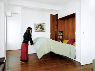 An architect couple use multifunctional furniture and a hydraulic Murphy bed with secret compartments to keep the exterior walls uncluttered and achieve a clean and lean look in their 650-square-foot Chelsea apartment.