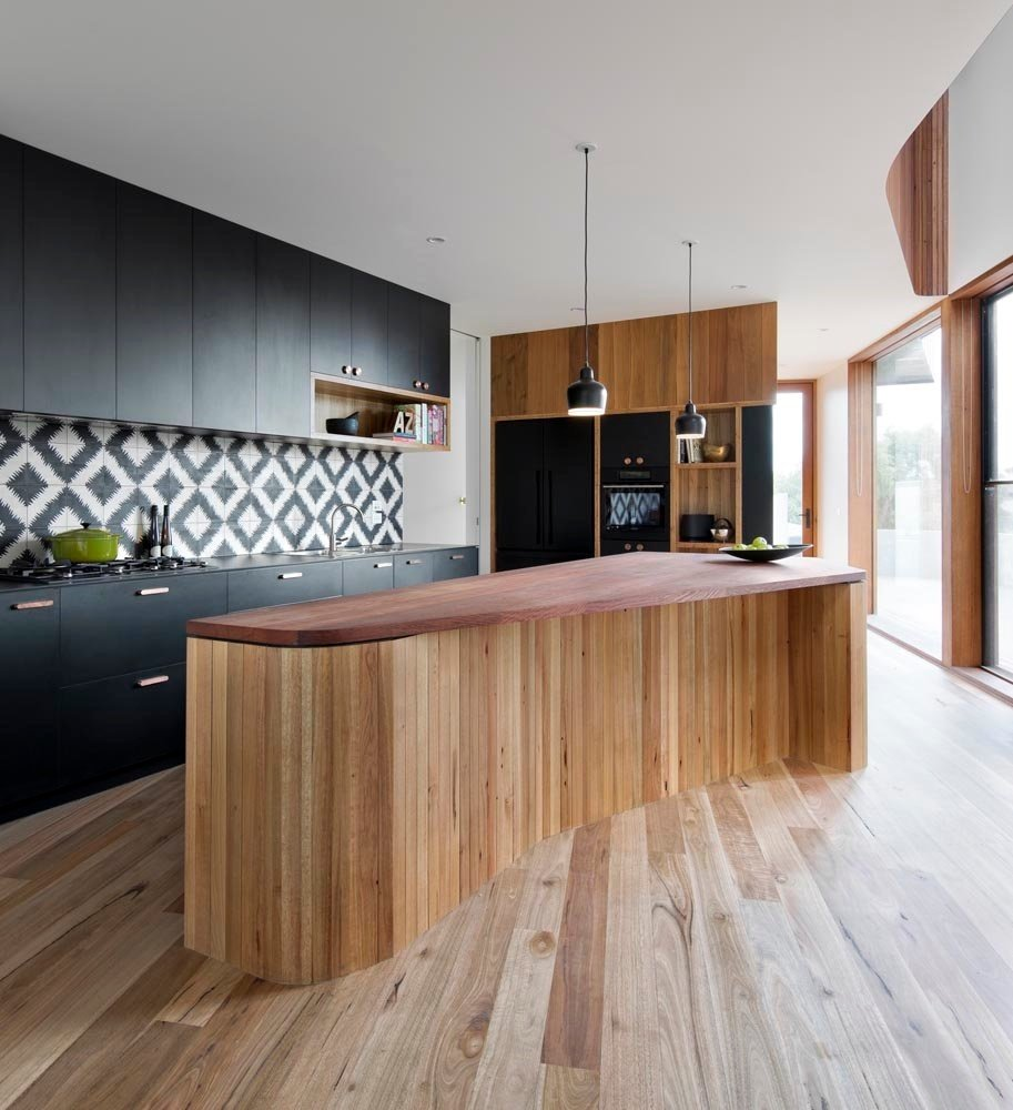 Kitchen, Wood Cabinet, Light Hardwood Floor, Pendant Lighting, and Wood Counter Eye-catching tiled splashback from Popham Design.  Super Cool Kitchen Islands by Erika Heet from How to Design a Kitchen That's Ideal For Entertaining—and Shop Our Picks