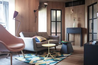 A green, yellow, blue and white print rug and matching cushion, a pastel pink armchair and plenty of bold geometrical shapes gives this apartment a slick, urbane vibe.