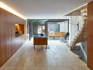 In this Edwardian house in London, the colors and textures of the brick walls that form the perimeter of the outdoor courtyard can be seen through floor-to-ceiling windows in the kitchen.