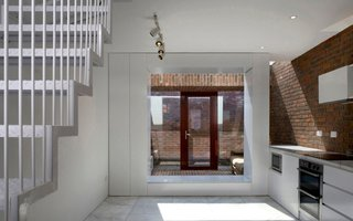 Inspired by the traditional red brick houses in Dublin, this home features exposed brick walls that begin in the interior kitchen, extend out to a skylit sitting area, and finally continue onto an outdoor courtyard.