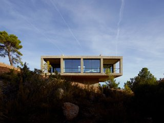 Set on the edge of Puertos de Beceite national park in Aragon, Spain, and available for vacation rentals, Casa Solo Pezo is a striking concrete square structure set on top of a smaller concrete square bass. Designed by award-winning and MoMA-exhibited Chilean architects at Pezo Von Ellrichshausen, this thoroughly modern residence has proportions and an interior layout that follows those of traditional Mediterranean homes with a strong indoor/outdoor connection. Its board-formed concrete exterior gives the building a texture and pattern that lend an almost organic, natural feel despite its very rectilinear form.