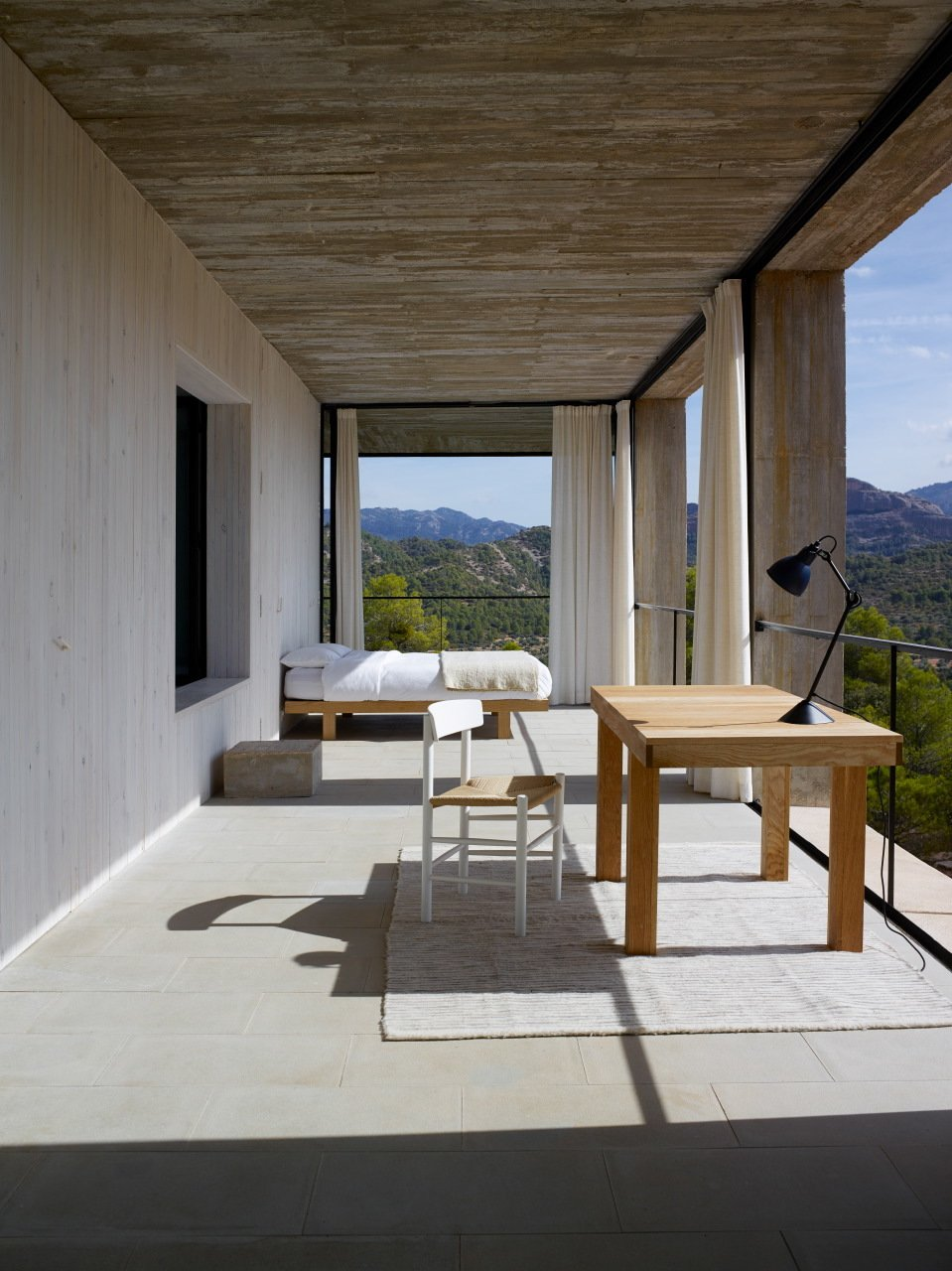 Bedroom, Table Lighting, Bed, and Chair Sitting on the edge of Puertos de Beceite national park in Aragon, Spain, is Casa Solo Pezo, the first property in the Solo Office collection of cutting-edge, architect-designed vacation rentals. Designed by the award-winning and MoMA-exhibited Chilean architects at Pezo Von Ellrichshausen, Casa Solo Pezo features a large concrete square structure that's set on top of a smaller concrete square base.  Photo 17 of 25 in 25 Modern Homes That Kill it With Concrete