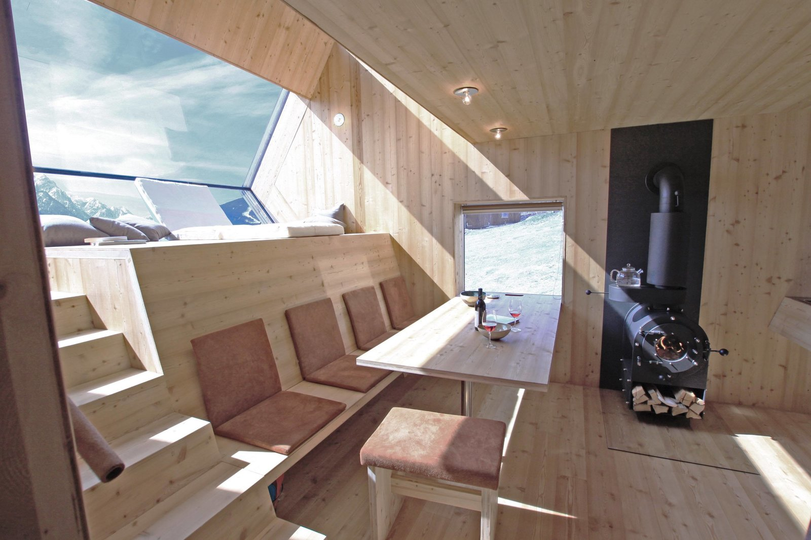 Dining, Bench, Table, Stools, Light Hardwood, Ceiling, Wood Burning, and Wall On the upper level, underneath a domed roof, sleeping areas and a bathroom allow guests to once again enjoy views of the mountains—this time from under a rain shower.   Best Dining Wood Burning Wall Photos from Stay in a Tiny Shingled Cabin in Austria That Resembles a Bird-Like UFO