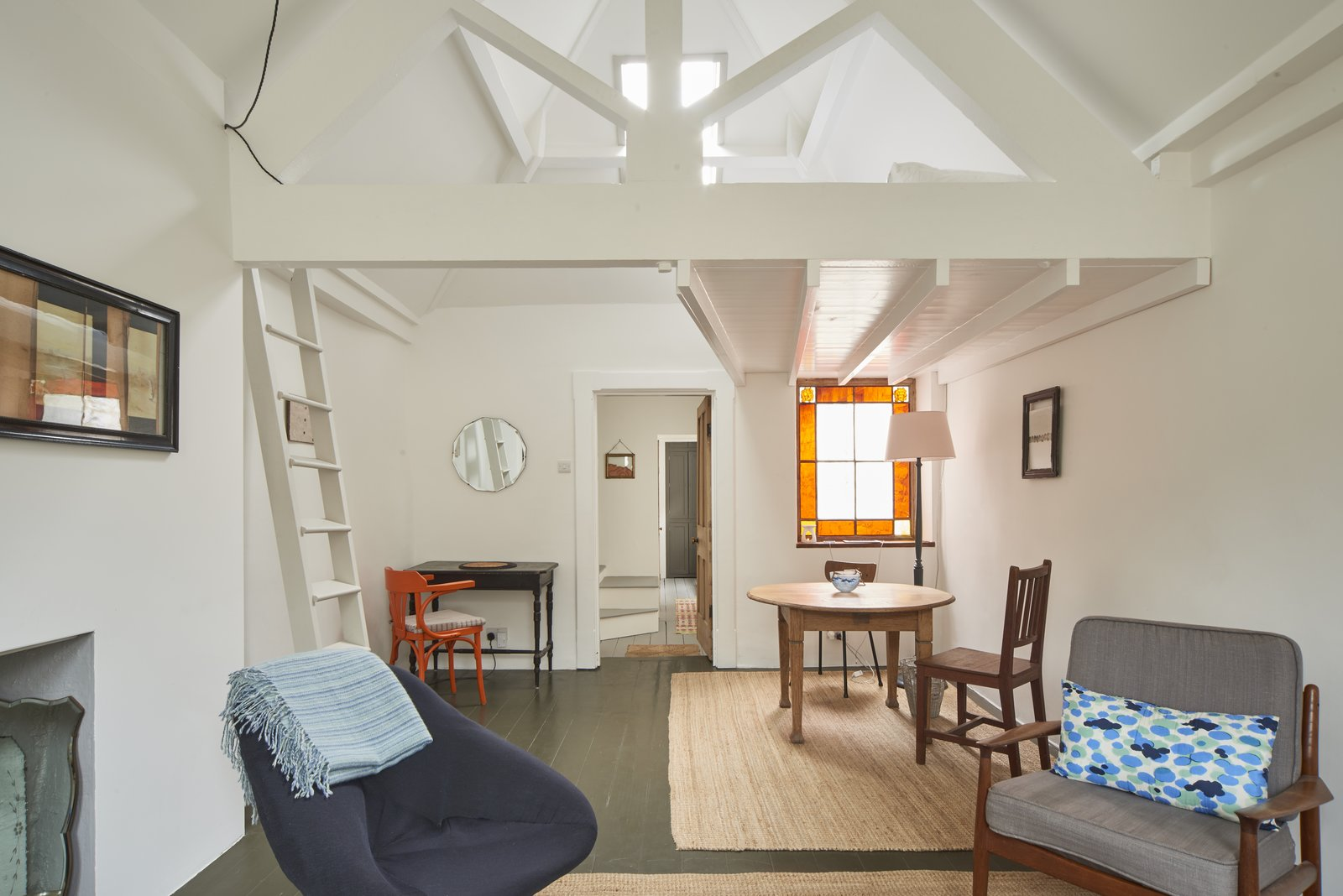 Living Room, Chair, Table, Lamps, Floor Lighting, Dark Hardwood Floor, Desk, and Rug Floor The quaint living space features a stained-glass window, lofted sleeping platform, vaulted ceilings, and arched-sash windows.  Photo 8 of 8 in 6 Best Dwell UK Apartments