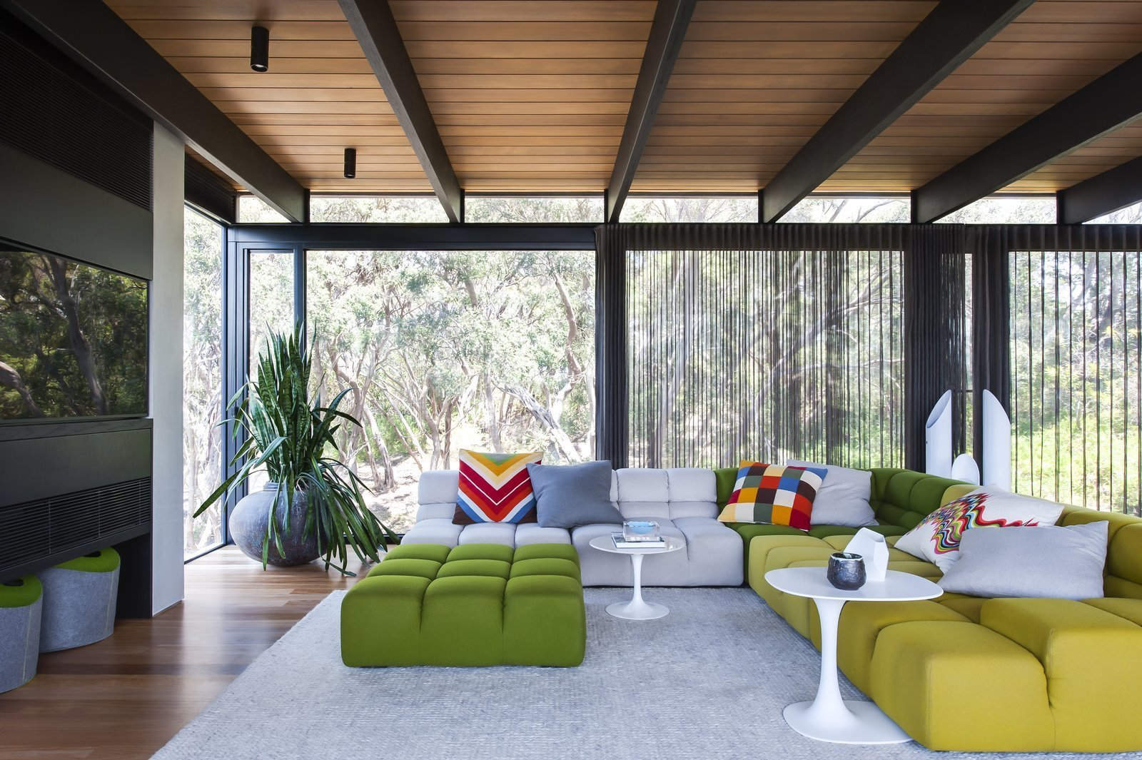 Living Room, End Tables, Ceiling Lighting, Storage, Sofa, Medium Hardwood Floor, and Rug Floor In this house in the Mornington Peninsula in the south of Melbourne, materials like concrete, natural stone, steel and cedar are perfect backdrops for architecture and interior design firm SJB to use bold colors and edgy midcentury furniture.  Best Photos from 11 Amazing Australian Homes