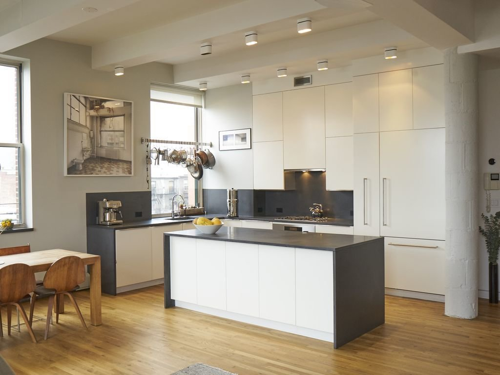 Kitchen, White Cabinet, Light Hardwood Floor, Ceiling Lighting, Range, Range Hood, and Drop In Sink Fitted with 11 massive windows that overlook both Brooklyn and Manhattan, this three-bedroom loft has a fully equipped gourmet kitchen makes it a great choice if you're planning on doing lots of cooking and eating in.  Photo 8 of 12 in Experience New York City's Eclectic Side at One of These Modern Short-Term Rentals