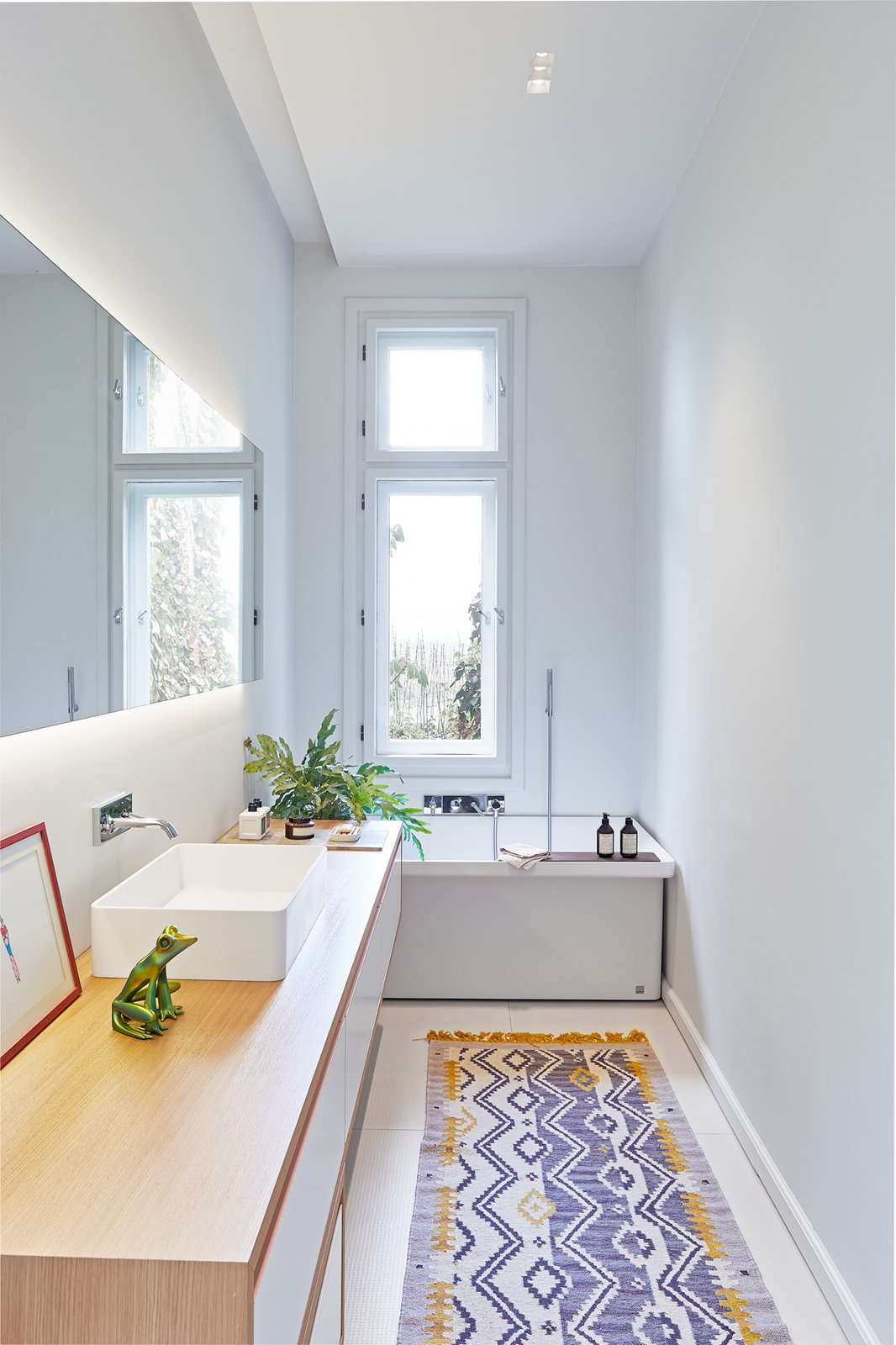 Bath Room, Wood Counter, Rug Floor, Vessel Sink, Alcove Tub, and Recessed Lighting Designed by Hungarian studio POSITION Collective, this 2,099-square-foot, two-story villa on Rezeda Street in the Pest area of Budapest is home to a family of four. Within, herringbone wood floors, geometric details on the ceilings, quirky lighting, furniture with interesting textures and colors, and framed artwork and photography come together to create a jaw-dropping contemporary home.  Photo 8 of 17 in A Family Villa in Budapest With Colorful, 1960s-Inspired Interiors