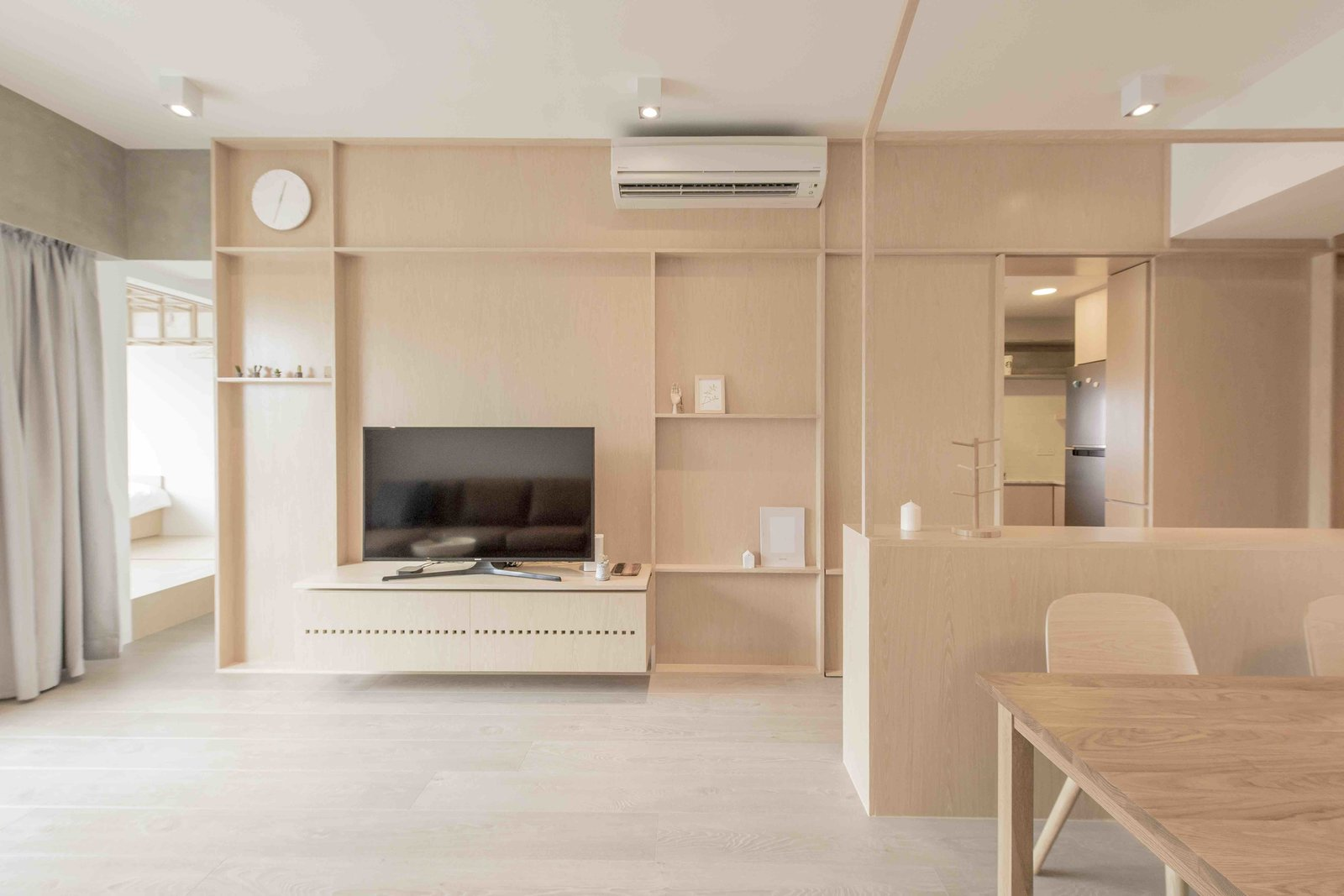 Living Room, Light Hardwood Floor, Ceiling Lighting, Storage, and Shelves A multifunctional plywood-and-wood veneer wall defines the living area of a simple yet elegant Hong Kong apartment.  Photo 2 of 15 in An Origami-Inspired Apartment in Hong Kong With Tons of Smart Storage