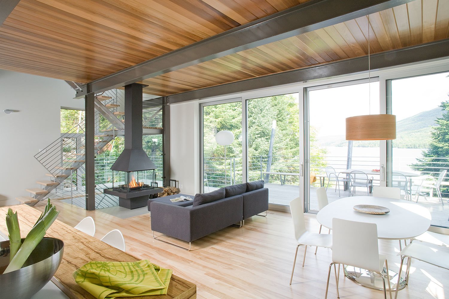 Living, Sofa, Chair, Table, Pendant, Light Hardwood, and Two-Sided Located on a steep slope that descends toward Archambault Lake, the house's elevated position presents magnificent views of the lake and surrounding forest.  Living Table Two-Sided Sofa Photos from 7 Incredible Modern Homes by Canadian Architect Paul Bernier