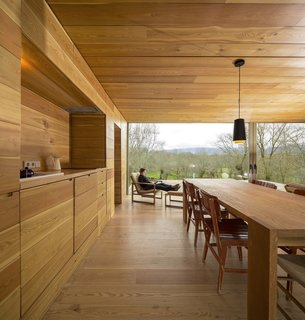Try using the same finish on your kitchen cabinets, walls, and ceiling. This creates an effect that allows everything to blend in seamlessly with the rest of the home. Case in point: this home employs a consistent wood palette.