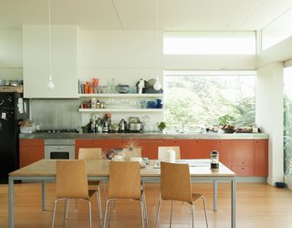 If you don't like handles sticking out from your cabinet doors, one clever idea is to have a hole drilled near the top of the cabinet door so that you can stick you finger in and pull the door open. These orange-painted MDF cabinets in a New Zealand beach house show how this technique can work brilliantly in cheery, low-key kitchen.