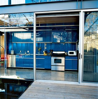 If you're a minimalist, you may prefer hingeless track doors over swinging doors with handles. In this steel-frame Texas home, the bright blue galley-style kitchen has no visible hinges, which makes it look like it's one with the similar-colored back wall.