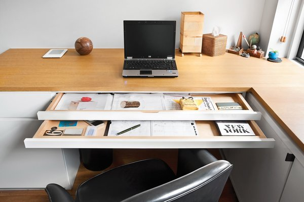 In the home office of a Manhatten studio apartment, each of the sliding trays in the office desk serves a different function.