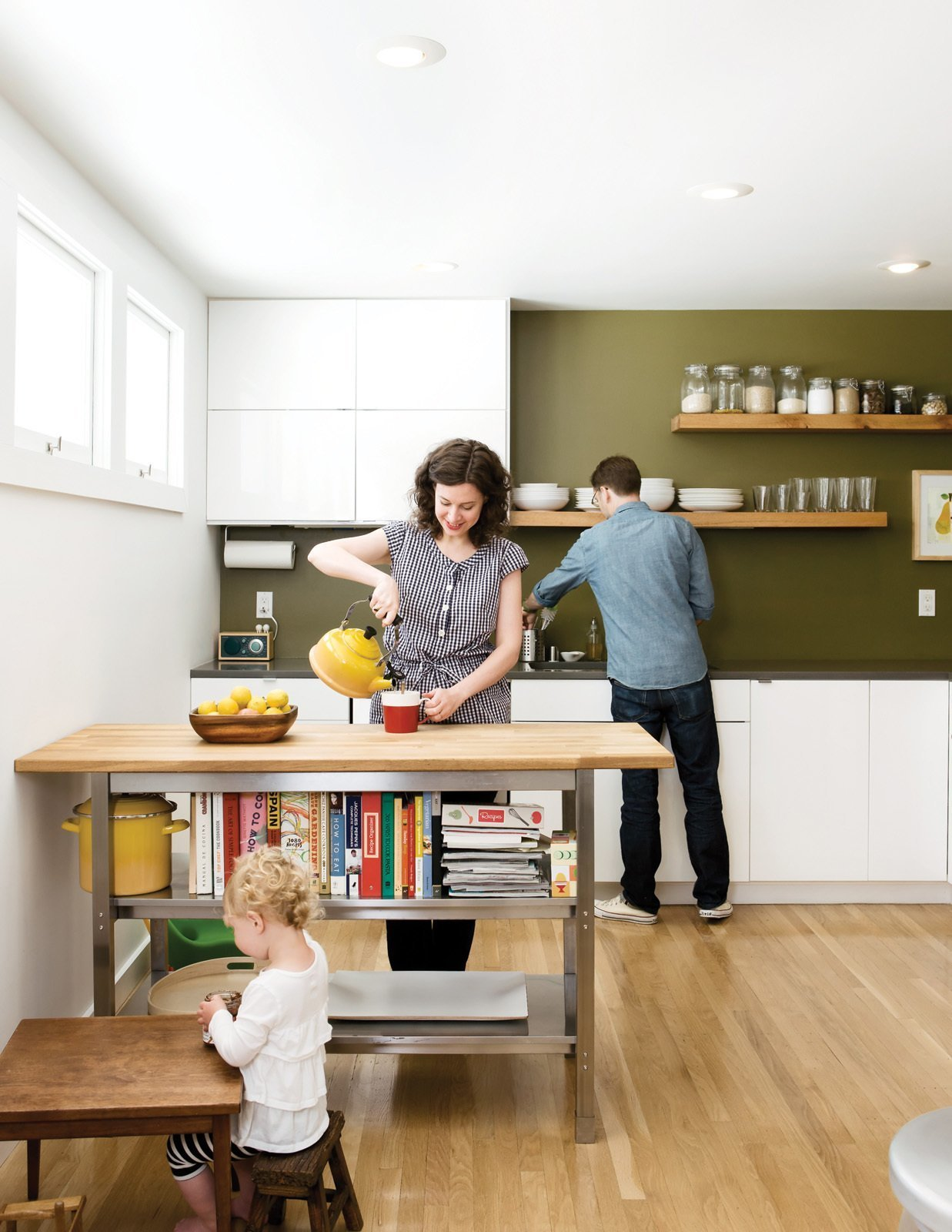 Kitchen, White Cabinet, Ceiling Lighting, Drop In Sink, Open Cabinet, Light Hardwood Floor, and Wood Counter Custom floating shelves and a book shelf under a movable island counter cleans a fuss-free, streamlined look in this kitchen.  Best Photos from 4 Decluttering Tips From Organizing Master Marie Kondo
