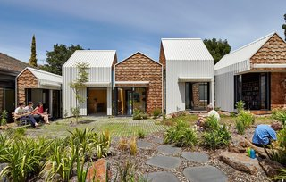 This Melbourne home is made up of a series of renovated gabled structures, and the contrast of its white steel panel and western red cedar shingle cladding emphasizes its geometric forms.