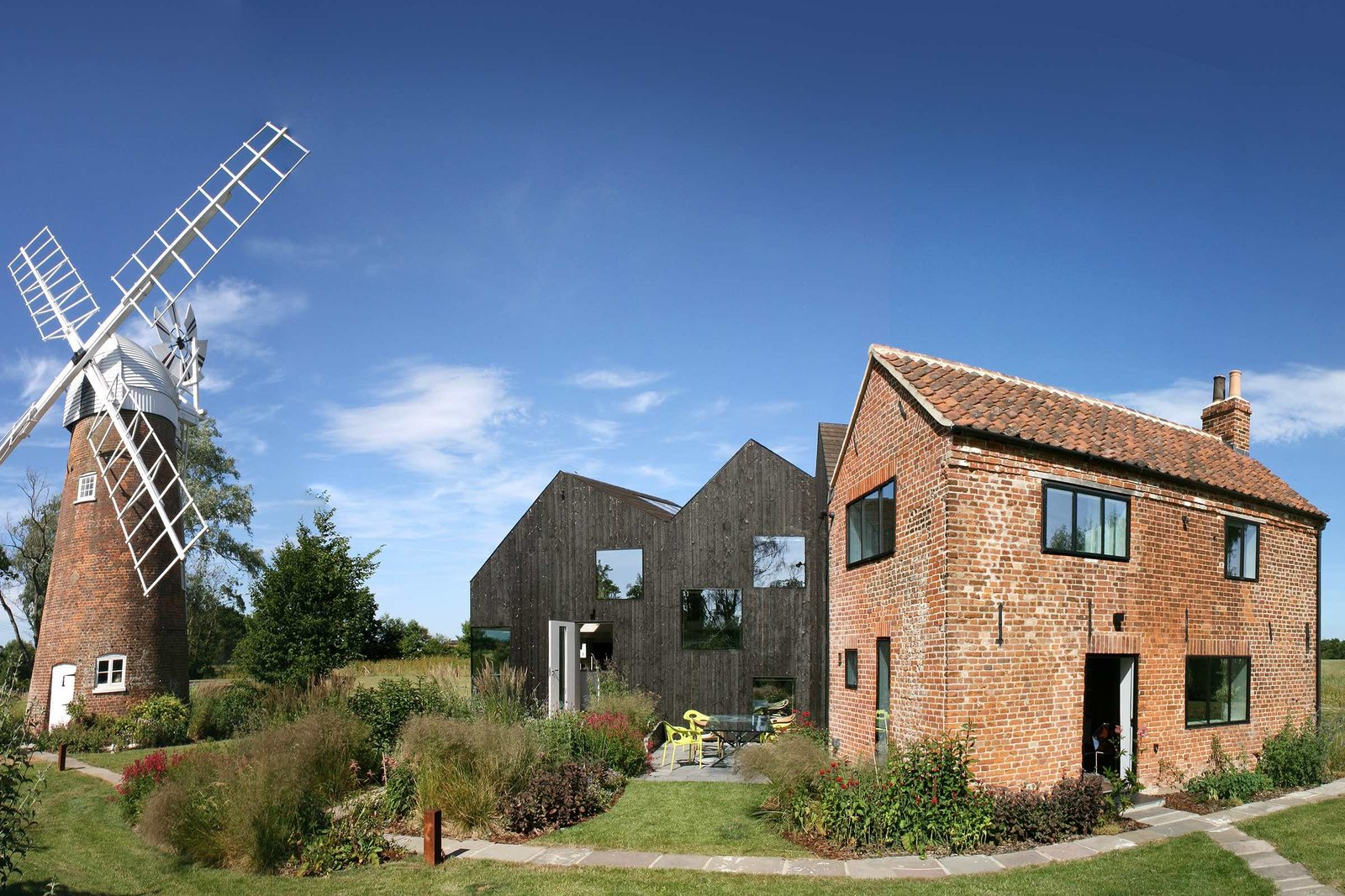 Exterior, House Building Type, Brick Siding Material, and Wood Siding Material This sensitively restore old mill keeper's cottage on the bank of Norfolk's River Ant has a new addition made from solid laminated wood that is a shadow of the original cottage.  Best Photos from 9 Traditional-Turned-Modern Cottages You Can Rent in the UK