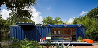 A narrow and long 8 by 40 feet empty steel shipping container in an artists' community in San Antonio, Texas serves a playhouse, garden retreat, and guesthouse for visiting creatives.
