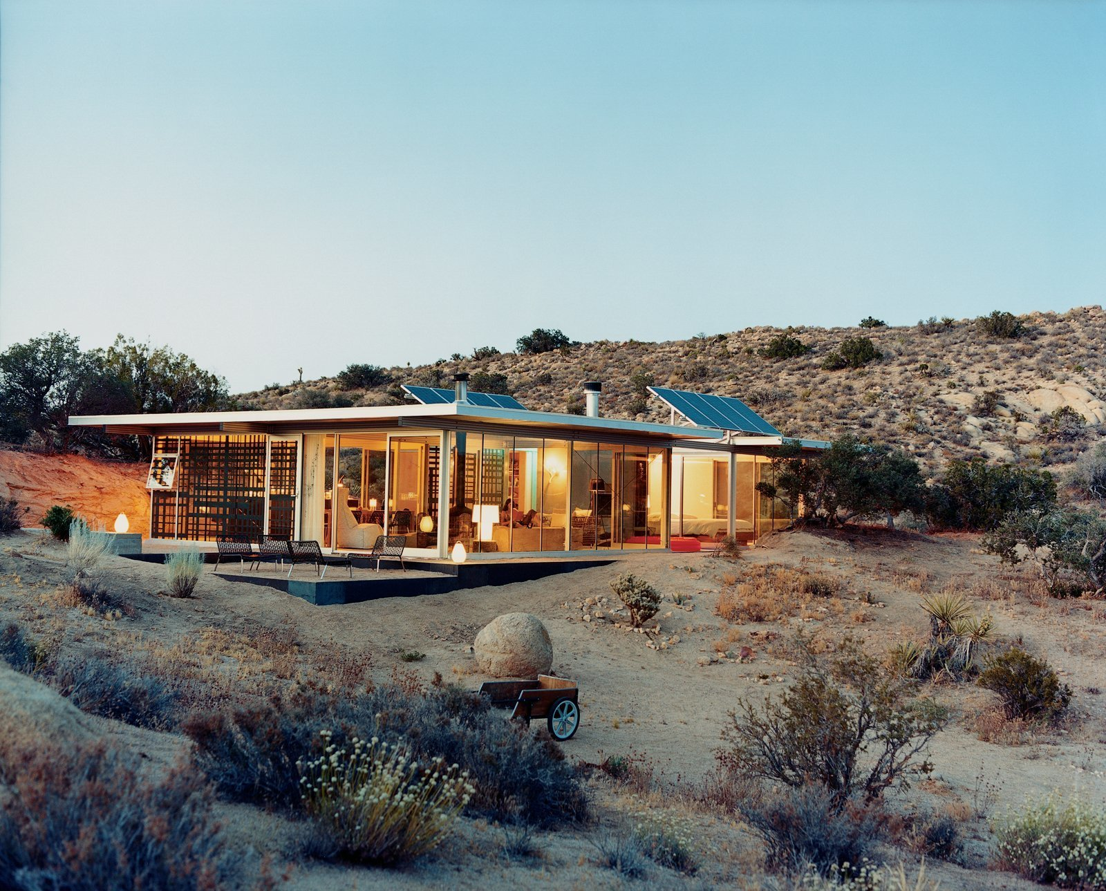 Exterior, Flat, Glass, Green, and Prefab Los Angeles–based design partners Taalman and Koch created this house in Pioneertown, California from prefabricated structural components, and included glass walls on which artists later applied surface graphics. Available for rent through Boutique Homes, this 1,100-square-foot house cost approximately $265,000 to build and is composed of a Bosch aluminum framing system and perforated steel decking roof. The interiors floor are equipped with radiant heating and cabinets were built out of Formica or plastic-laminated plywood.  Best Exterior Glass Green Photos from 7 Incredible Prefab Homes You Can Rent For Your Next Holiday