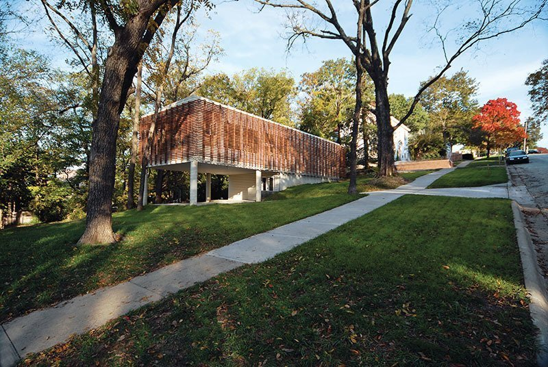 Exterior, Metal Siding Material, and House Building Type To tackle the challenges of a steep slopping site and a tight budget, architect Dan Rockhill used a slatted exterior screen of Cumaru wood to shields inexpensive metal sidings for this Kansas home.  Photos from 9 Best Homes With Interesting Screened Facades