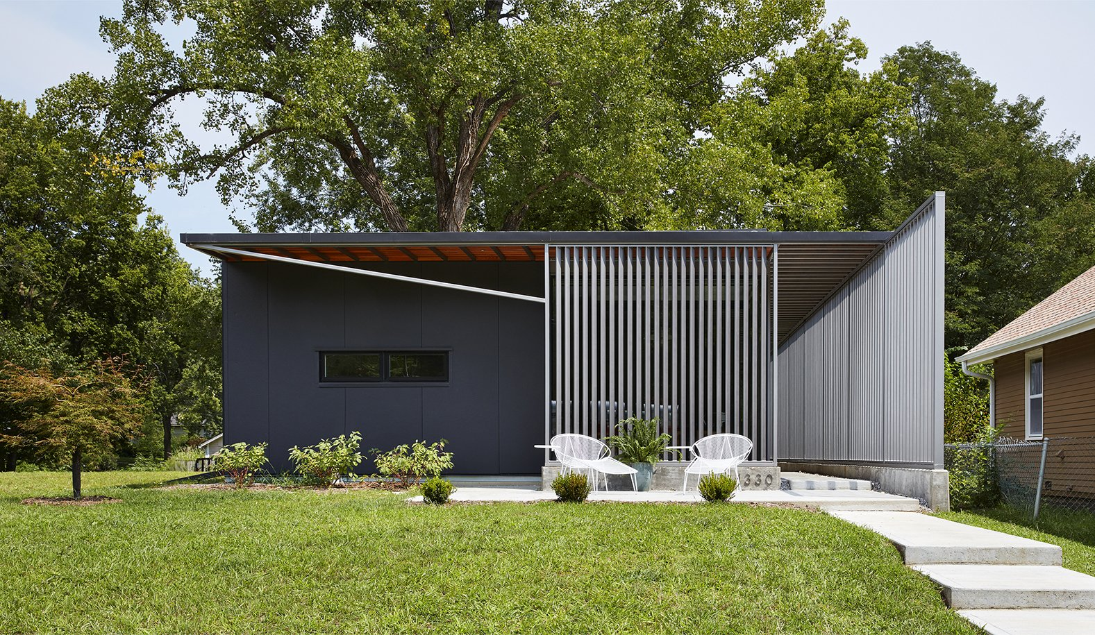 Exterior, Flat RoofLine, House Building Type, and Metal Siding Material Using insulted metal panels that were rejected from the construction of a tennis center nearby, this sustainable home in Kansas by Studio 804 was inspired by the prefab Lustron houses that were developed in the United States after World War II.  Photos from 9 Best Homes With Interesting Screened Facades