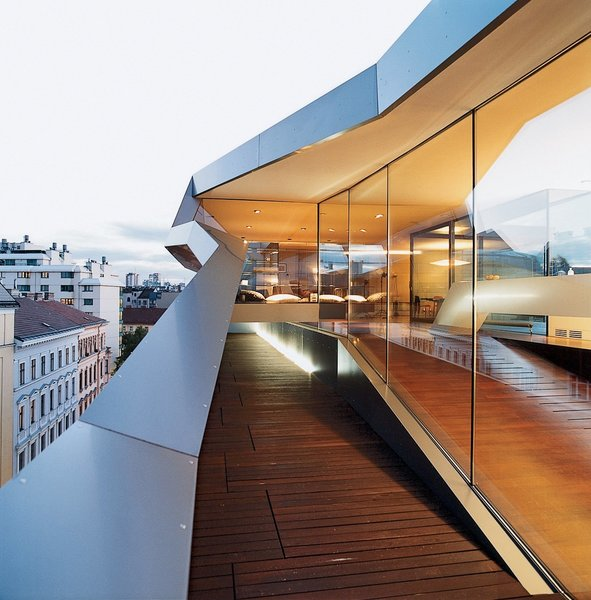 Using lightweight steel skeleton construction, Vienna architect Delugan Meissl boldly inserted this dazzling, modern Vienna penthouse in between traditional rooftops of the city's Wieden district, on top of an old building.