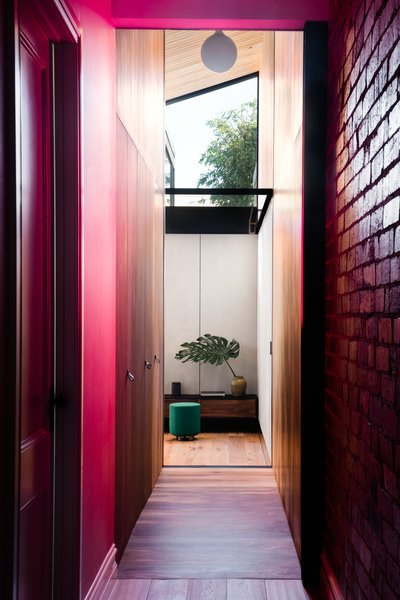 Home to architect Michael Artemenko, co-director of FIGR Architecture Studio—along with his wife Emma and their young daughter—this renovated heritage home in the Melbourne suburb of Cremorne uses a portal-like corridor painted a vibrant pink to connect the original period home to a new wing.