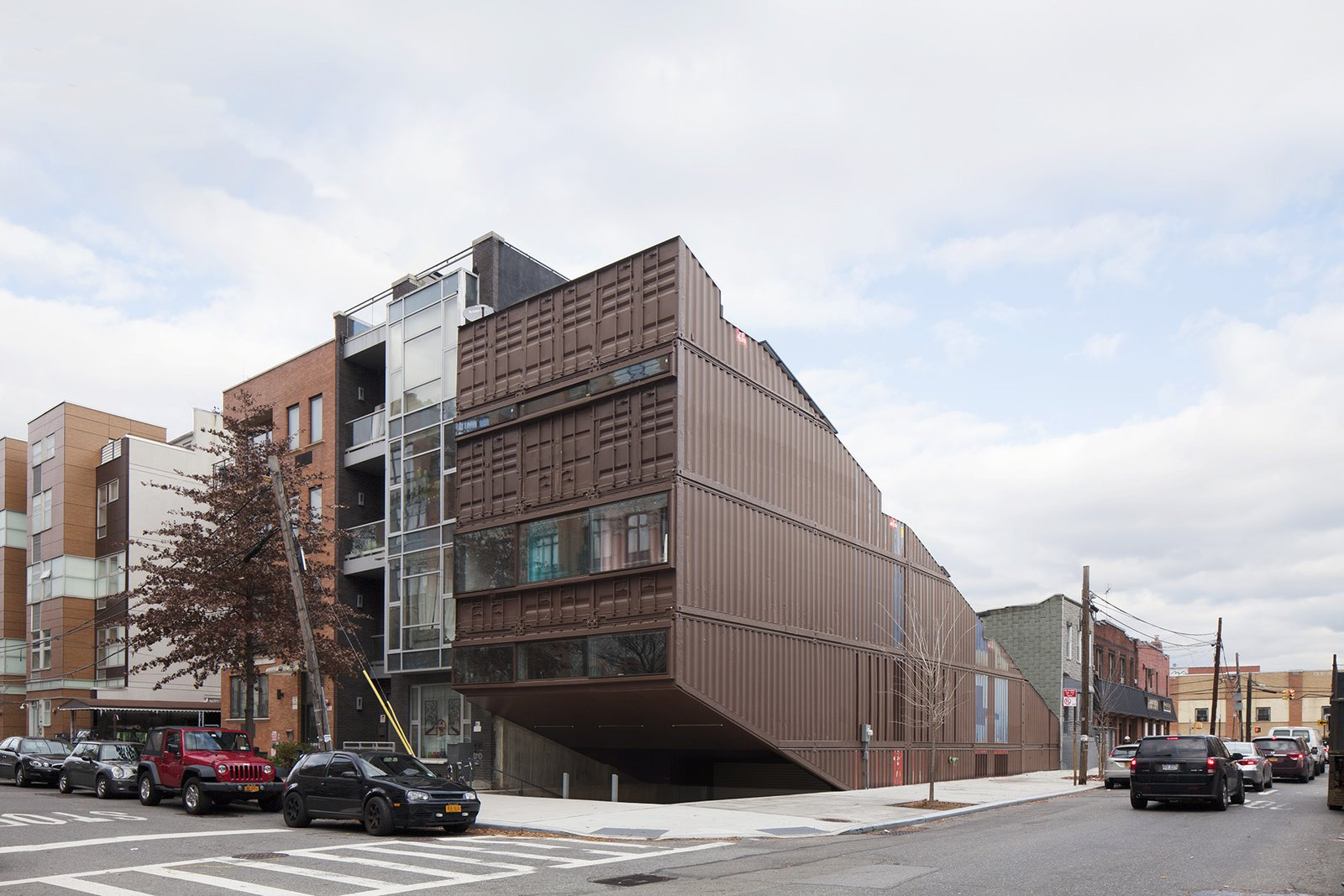 Exterior, House Building Type, Shipping Container Building Type, and Metal Siding Material Sited on a typical 25-by-100-foot corner lot in Brooklyn's Williamsburg neighborhood, this 5,000-square-foot residence was built with 21 stacked shipping containers cut diagonally along the top and bottom to create a step-like structure with four tiered levels and a small pool between the two lower levels.  Designed by LOT-EK, the construction process optimized the use of shipping containers by recombining all the leftovers from creating the diagonal cut.  Photo 2 of 13 in An Amazing Home in Brooklyn Made Out of 21 Shipping Containers