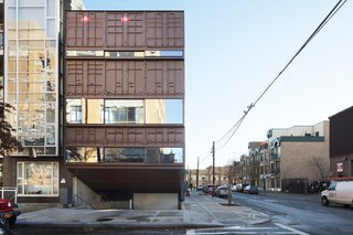 Sited on a typical 25-by-100-foot corner lot in Brooklyn, this 5,000-square-foot residence was built with 21 stacked shipping containers cut diagonally along the top and bottom to create a step-like structure with four tiered levels and a small pool between the two lower levels.