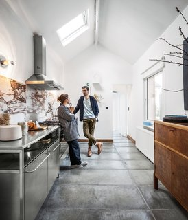 Passionate about recycling, a Belgium designer couple Michaël Verheyden and Saartje Vereecke reused a beautifully-vein marble top from a heavy table from Vereecke's parents' house as the backsplash for their kitchen.