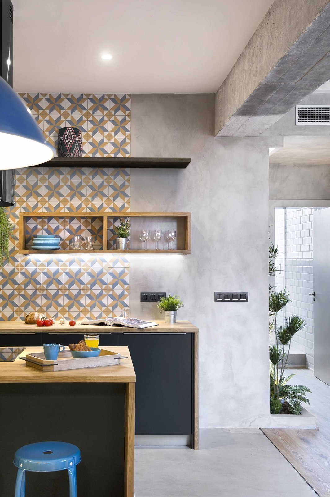 Kitchen, Wood, Cooktops, Medium Hardwood, Concrete, Ceramic Tile, Pendant, Recessed, and Open Geometric-patterned, hydraulic-imitation tiles from Portuguese brand Recer in grey, mustard, and white used for the backsplash, and a feature wall gives this Barcelona apartment plenty of vibrant charm.  Best Kitchen Cooktops Recessed Wood Open Photos from 12 Brilliant Kitchen Backsplash Ideas