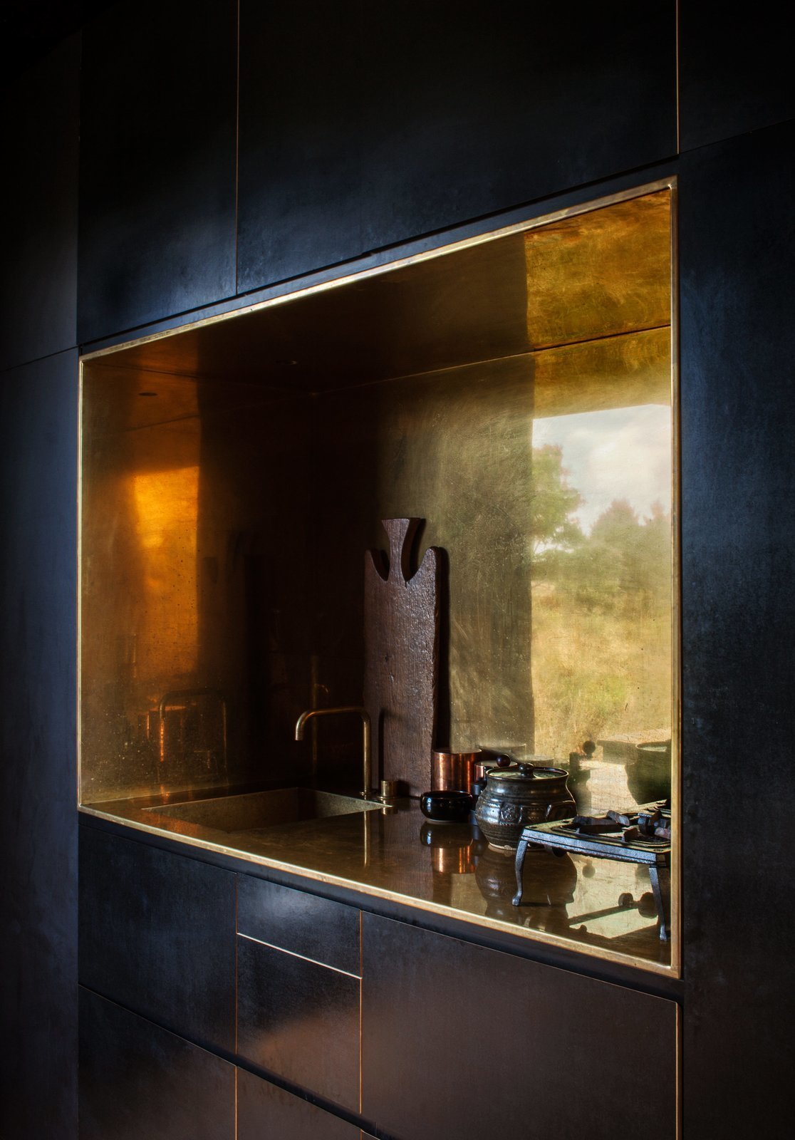 Kitchen, Drop In Sink, and Metal Backsplashe In this off-the-grid cabin in New Zealand is a polished brass-lined kitchen niche with a matching tap by Arne Jacobsen for Vola that contrasts the otherwise spare, black, minimalist interiors.  Photo 9 of 12 in 12 Brilliant Kitchen Backsplash Ideas