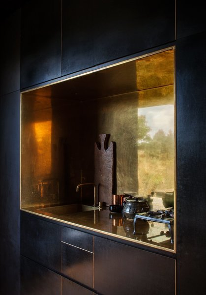 In this off-the-grid cabin in New Zealand is a polished brass-lined kitchen niche with a matching tap by Arne Jacobsen for Vola that contrasts the otherwise spare, black, minimalist interiors.