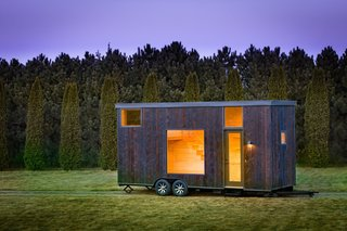 Named ESCAPE One, this tiny 276-square-foot Park Model RV trailer has an exterior of Shou Sugi Ban siding and light colored pine wood interiors.