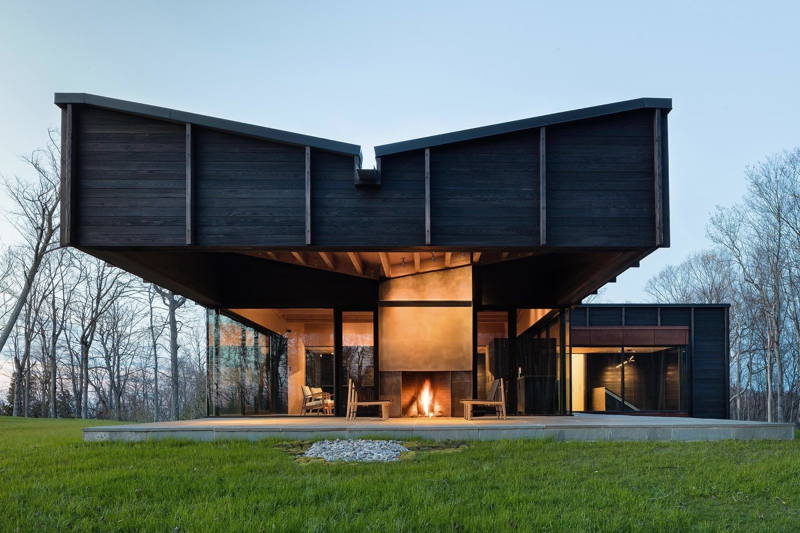 Exterior, House Building Type, Wood Siding Material, and Butterfly RoofLine With a textured skin of Shou Sugi Ban, Michigan Lake House, designed by New York firm Desai Chia Architecture in collaboration with Michigan firm Environment Architects, dramatizes the play of light and shadows as the sun moves it through the day.  Best Photos from 10 Striking Homes Featuring the Japanese Art of Shou Sugi Ban