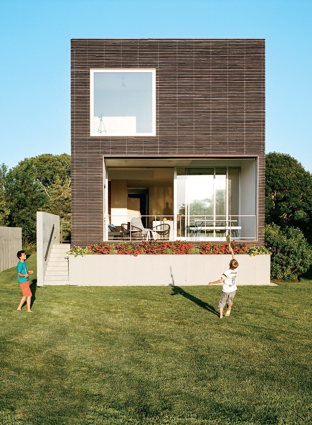 Outdoor, Back Yard, Trees, Vertical Fences, Wall, Grass, Raised Planters, and Small Patio, Porch, Deck This Rhode Island home has a modernist box structure with an exterior made of milled, charred, brushed, and oiled cypress slats manufactured by Delta Millworks.  Photo 15 of 15 in 10 Striking Homes Featuring the Japanese Art of Shou Sugi Ban