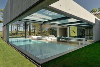 In the coastal town of Cascais, in an area known as the Portuguese Riviera, is this 11,840-square-foot concrete, wood, and glass home designed by Portugal-based firm Guedes Cruz Architects, which boasts a pair of large swimming pools on two levels.