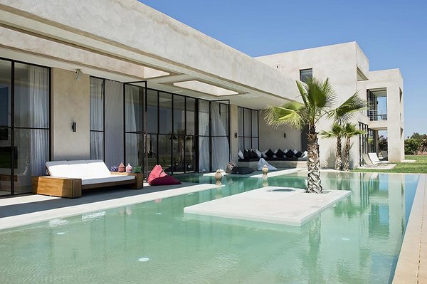 Just 25 minutes from the Medina of Marrakech, this contemporary Moroccan villa, designed by Algerian architect Imaad Rahmouni, celebrates Mediterranean living with lush gardens, a stunning indoor/outdoor pool, retractable, floor-to-ceiling windows, and a large semi-covered terrace with views of the Atlas Mountains.