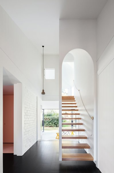 This renovated arts and craft family home in Sydney's leafy North Shore has an arched main entrance at the front of the house, and a narrow floating staircase with a threshold that mimics the arch on the façade.