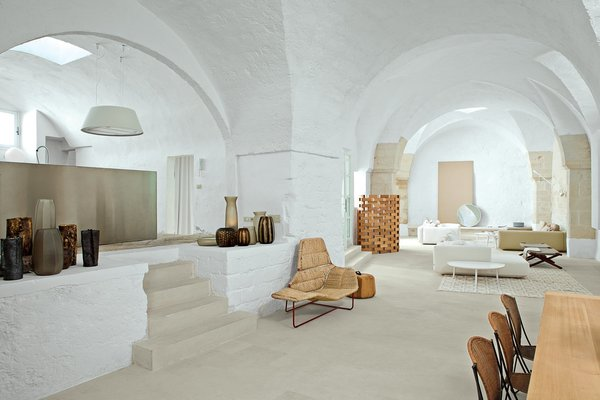 The arched walls and thresholds of this former 17th-century oil mill residence in Salento, Puglia serves as a dramatic backdrop for its Italian designer owners to showcase their contemporary custom creations and iconic, modern Italian furniture.
