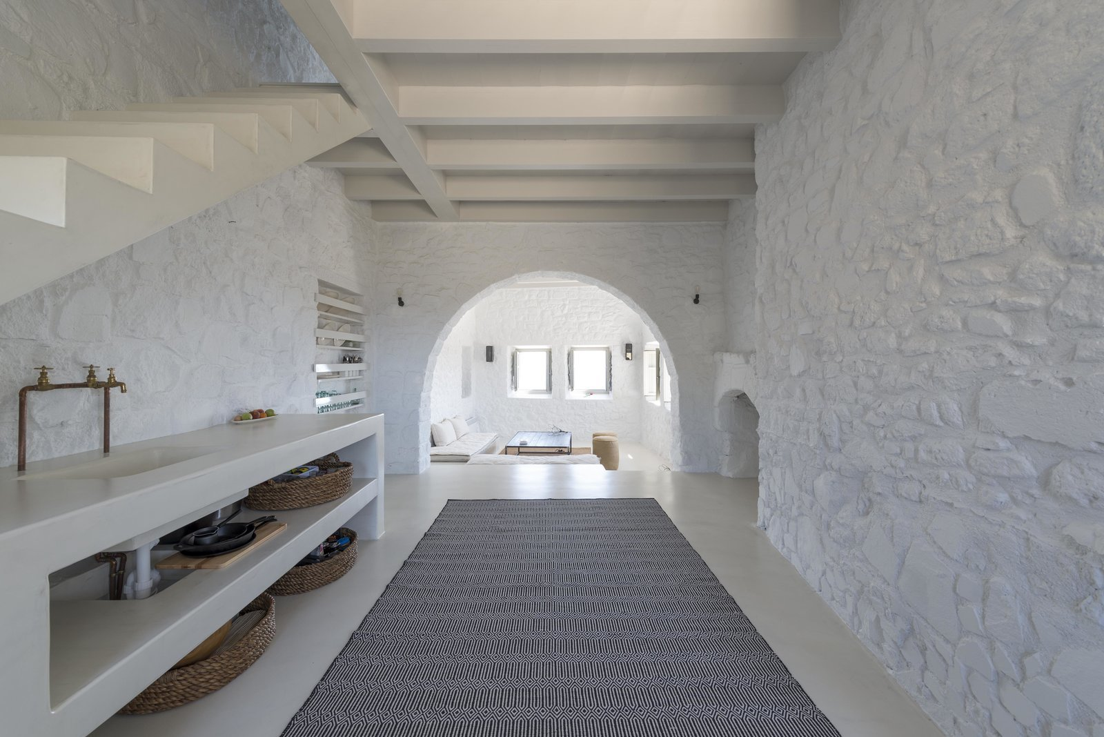 Kitchen, Wall Lighting, Rug Floor, and Open Cabinet Within this minimalist villa on the Greek island of Nisyros are vaulted ceilings, arched doorways, wood beams, white washed walls and clean, contemporary furniture in white, taupe, cream and coffee tones.  Photo 10 of 11 in Discover 10 Impressive Spaces With Arched Windows and Doors