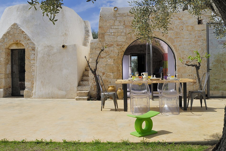 Outdoor, Back Yard, Trees, Grass, and Large Patio, Porch, Deck This restored and renovated traditional ancient trullo home in the commune of Ostuni in Puglia has an arched doorway constructed of locally-harvested lime and quarried stone, which was fitted with a full-height, pivoting glass door.  Photo 11 of 11 in Discover 10 Impressive Spaces With Arched Windows and Doors