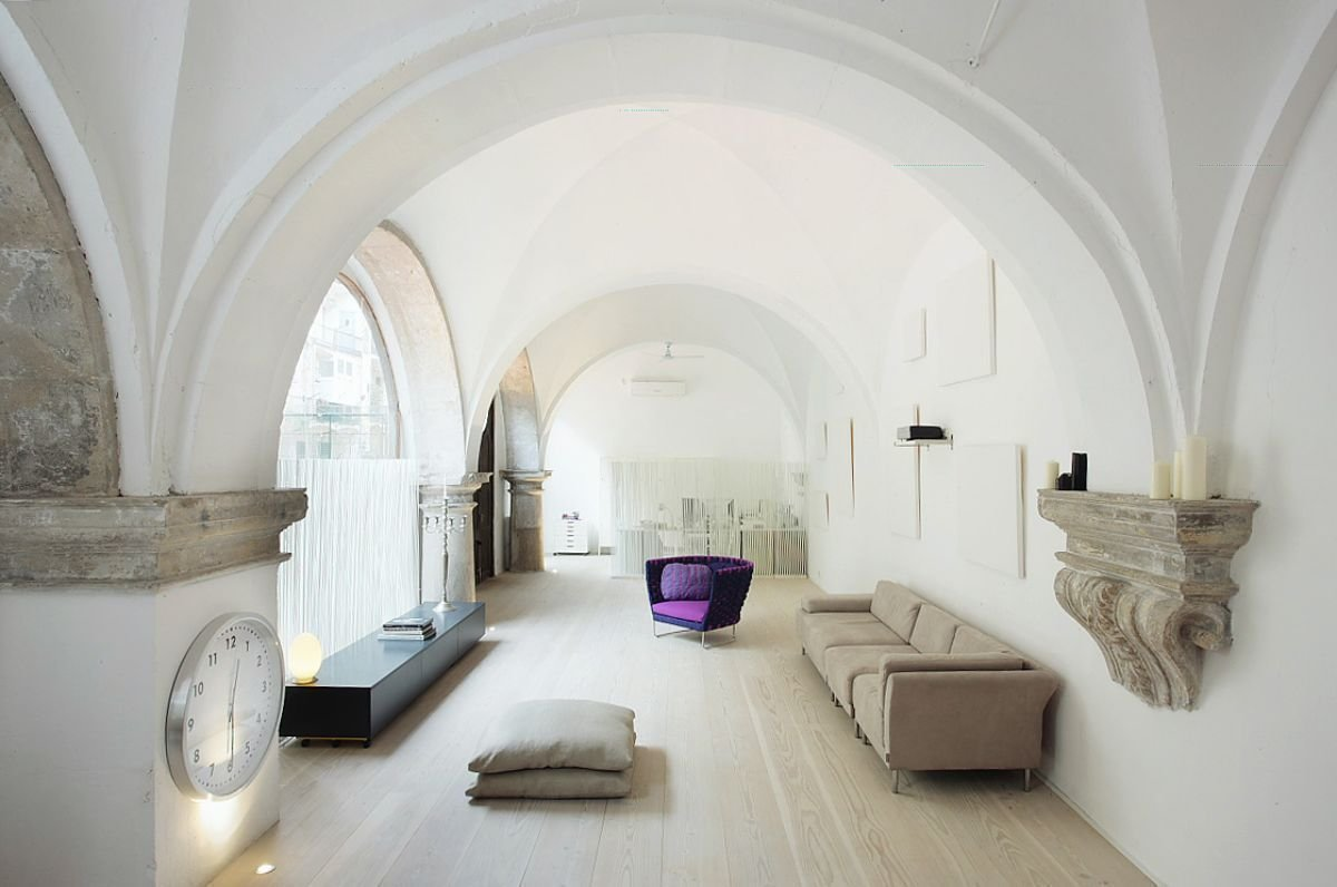 Living Room, Sofa, and Media Cabinet Vaulted cloisters in Barcelona that date back to the 1600s were converted into a vaulted residence with hand-carved stone features columns and arched stained glass windows.  Photo 2 of 11 in Discover 10 Impressive Spaces With Arched Windows and Doors