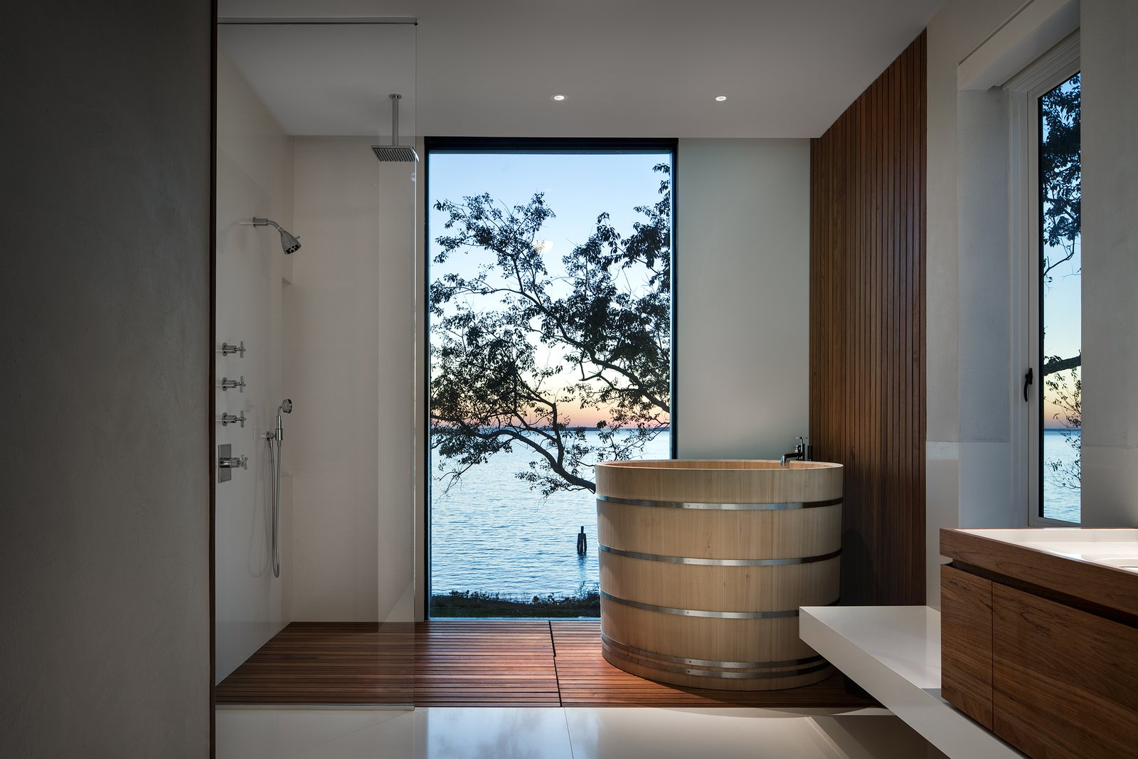 Bath Room, Freestanding Tub, Recessed Lighting, Open Shower, and Medium Hardwood Floor Sited on a sloping plot in Suffolk County, New York, this cantilevered house takes full advantage of its forest-meets-sea locale. Designed, built, and furnished by New York City-based firm Leroy Street Studio, this 5,935-square-foot home was born from the client's request to create a warm and stylish modernist house that would be intimate enough for private family retreats, yet impressive and expansive enough for entertaining large groups.  Photo 11 of 13 in An Incredible Cedar-Clad House Captures Views of the Sea and Forest